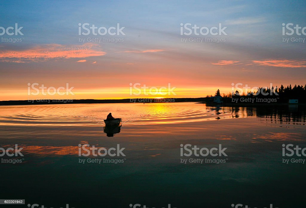 Outboard Boat Silhouetted by Sunrise. stock photo