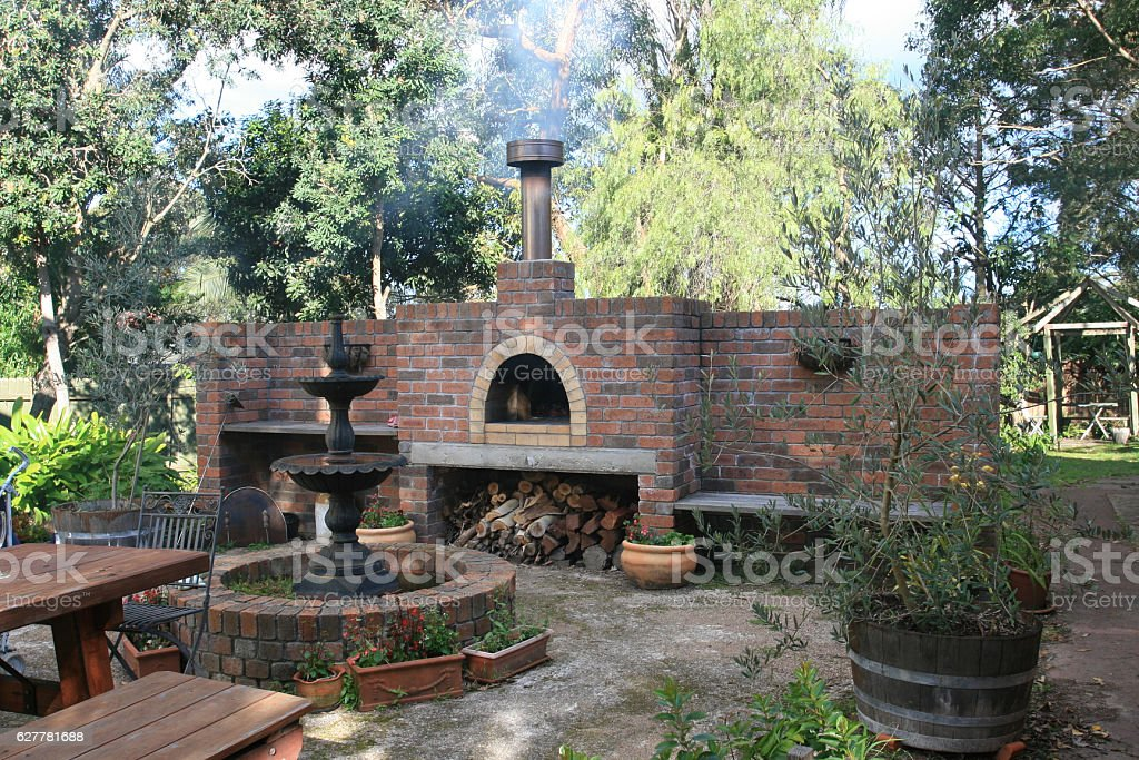 outdoor brick pizza oven and fountain stock photo