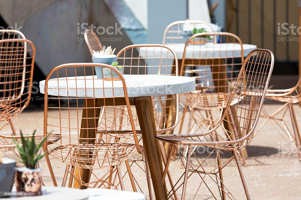Outdoor cafe with round tables and aluminium modern chairs stock photo