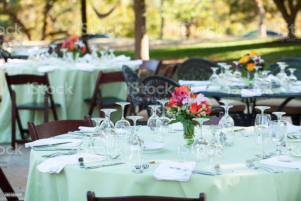 Outdoor tables with place settings for evening dinner.