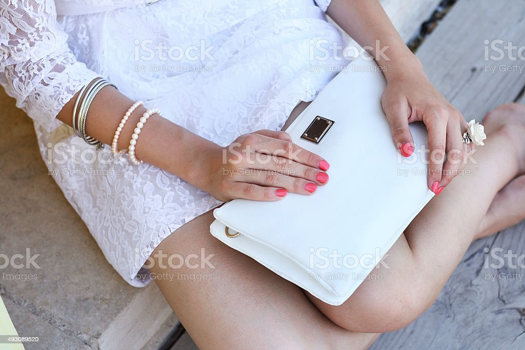 Outdoor fashion young woman hold white clutch handbag stock photo