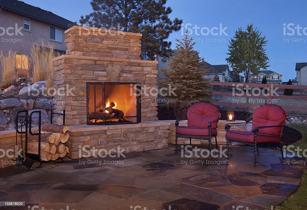 Outdoor flagstone platform with fireplace, chairs stock photo