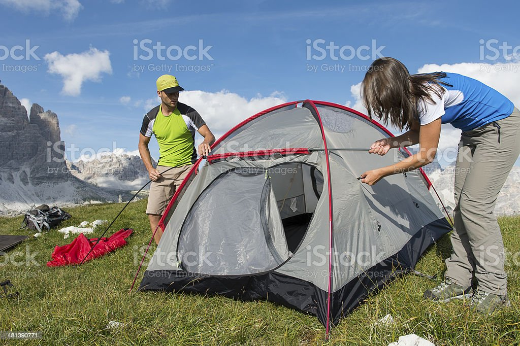 outdoor friends put a tent together royalty-free stock photo