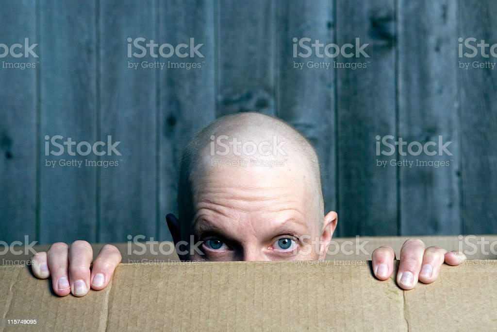 Outdoor funny picture balding woman peaking out of box stock photo