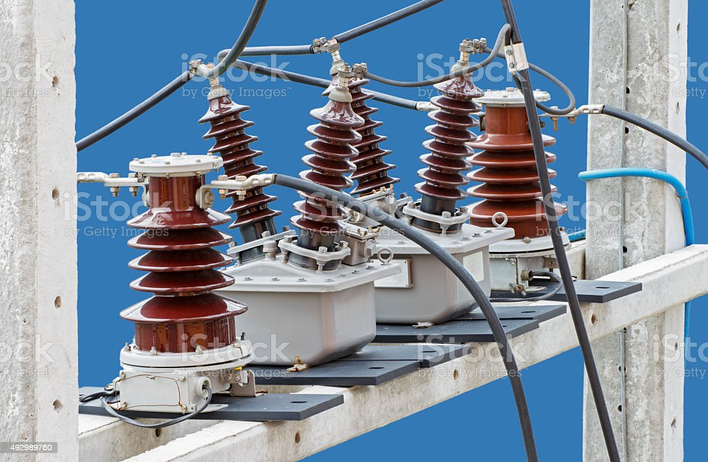 Outdoor High Voltage Instrument Transformers isolated on blue background stock photo