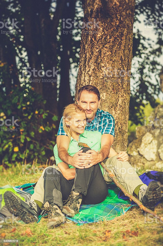 outdoor hiking couple taking a rest under a tree stock photo
