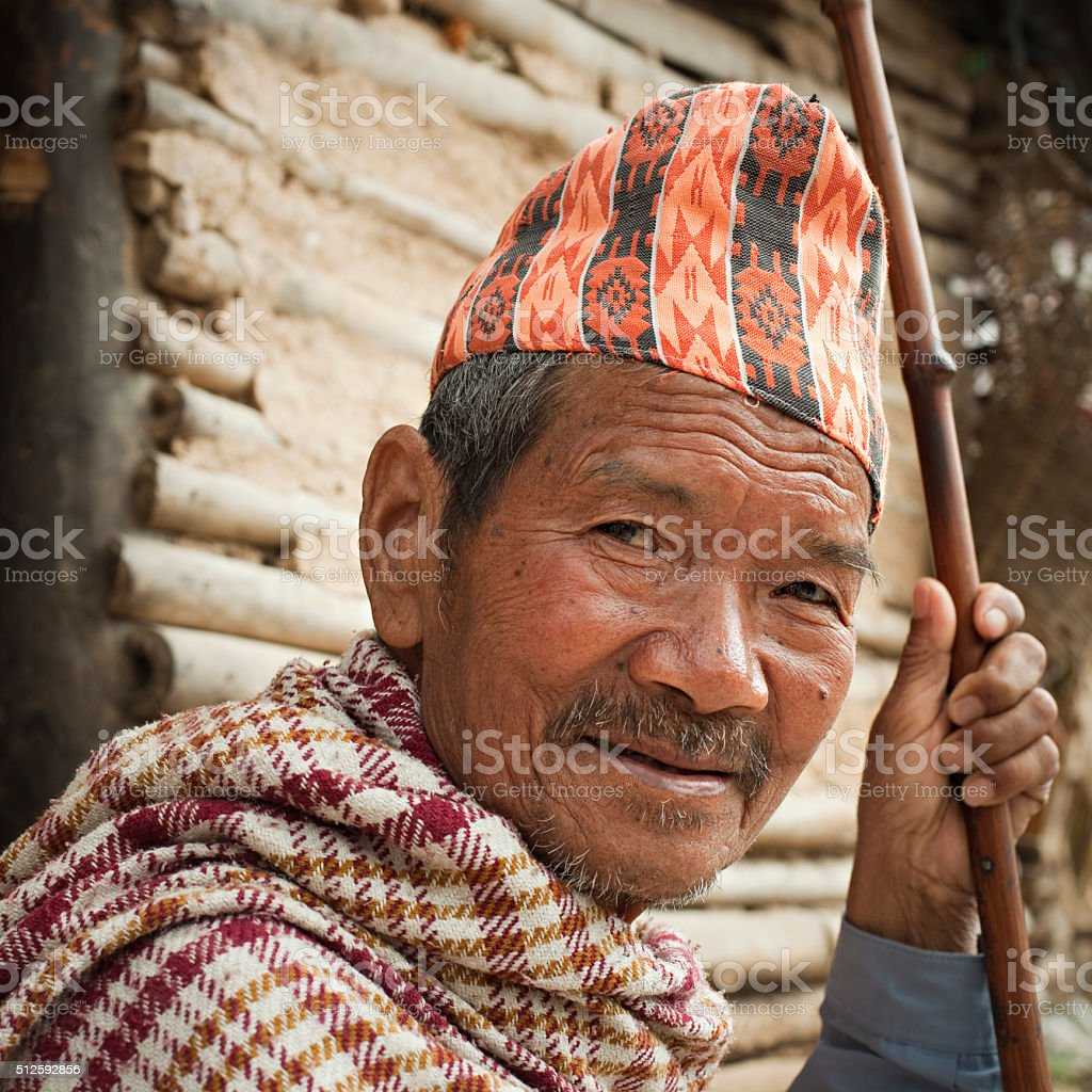 Outdoor image of senior Nepalese peasant man holding a stick. stock photo