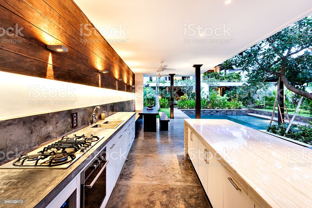 Outdoor kitchen with a stove an countertop next to garden including a...
