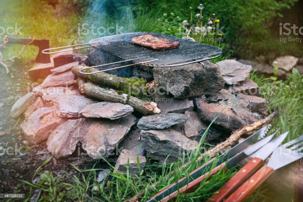 Outdoor life, grilling a steak on the campfire stock photo