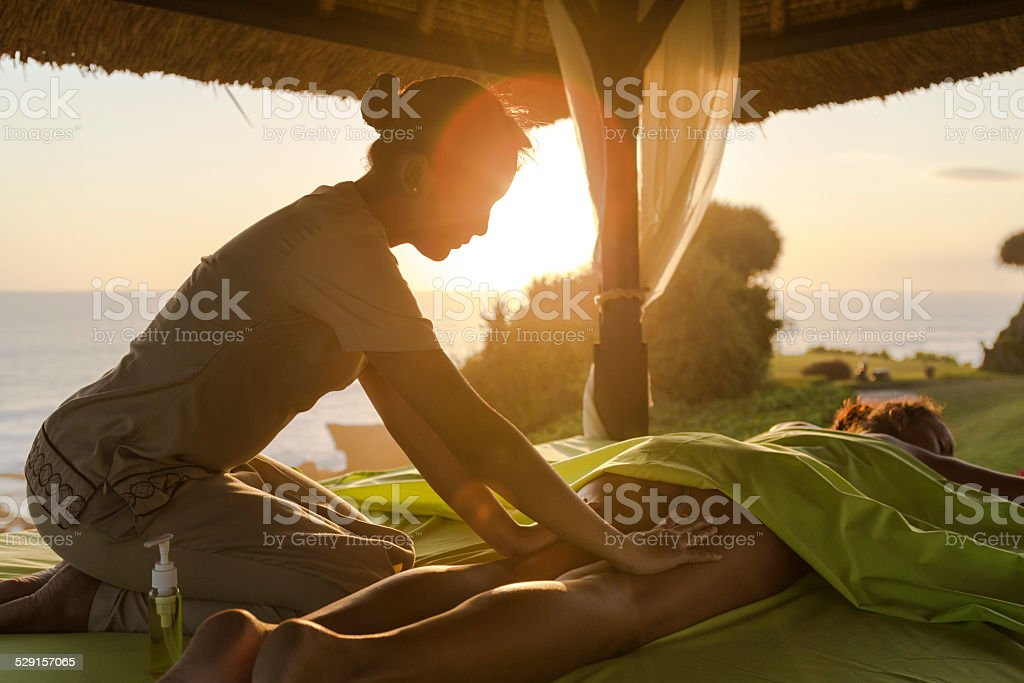 Outdoor massage at sunset by the seaside stock photo