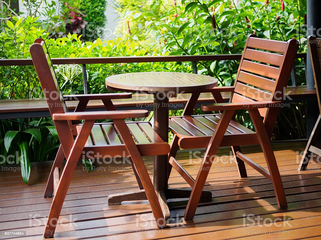 Outdoor Patio Furniture set of brown wooden, green tree background in...
