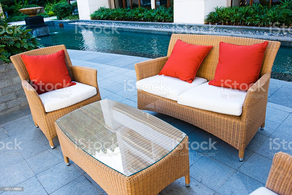 Outdoor patio furniture with red pillows by water fountain stock photo