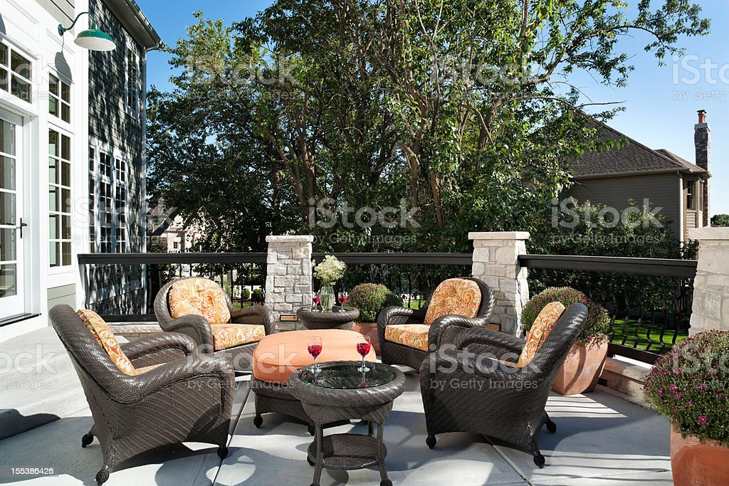 Wicker outdoor furniture decorates a homes lovely outdoor patio on a...