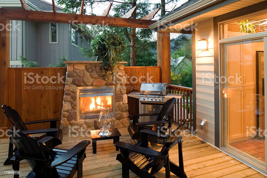Outdoor patio with fireplace, chairs and barbeque grill royalty-free stock photo