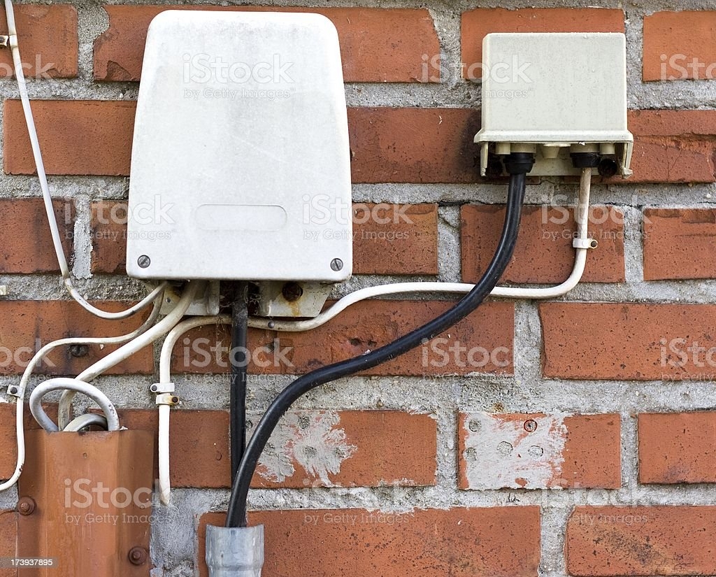Outdoor phone connection wires attached to red brick wall. royalty-free stock photo