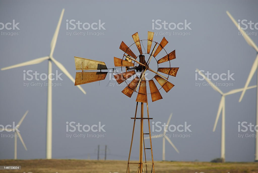 Outdoor photo of rusted windmill surrounded by wind turbines stock photo