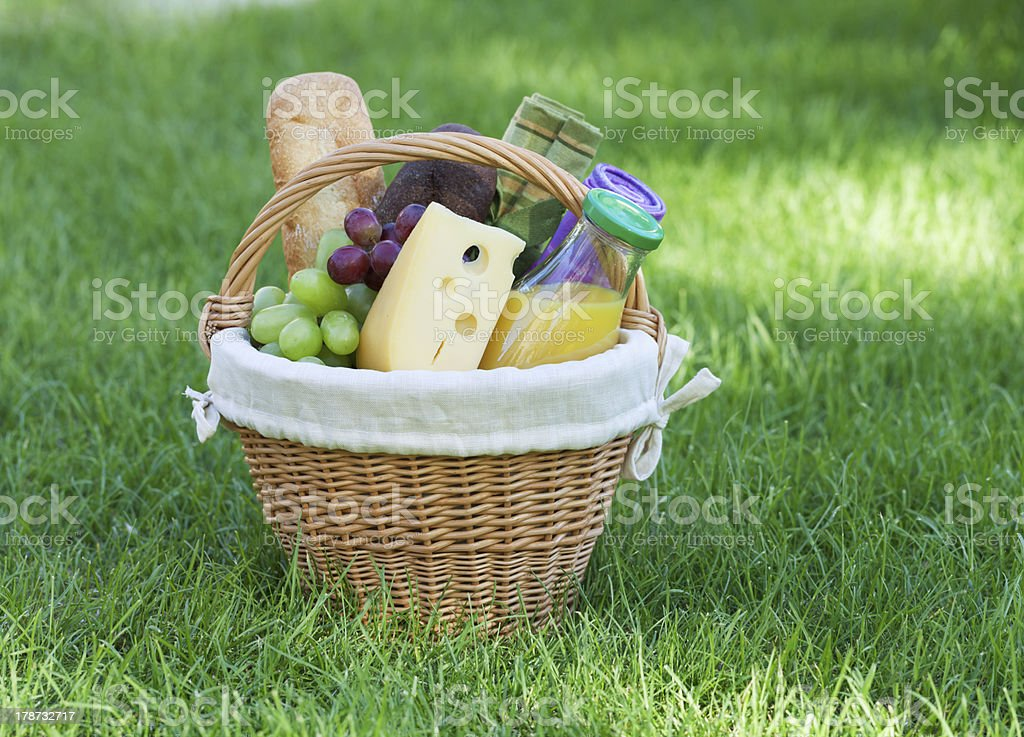 Outdoor picnic basket on green lawn royalty-free stock photo