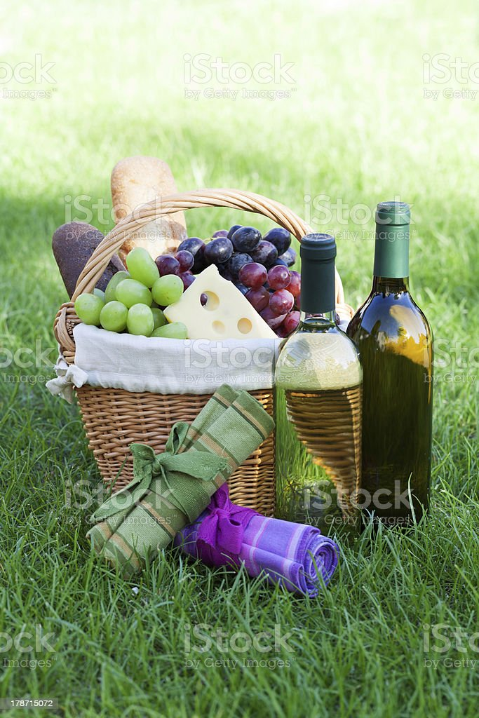 Outdoor picnic basket with wine on lawn royalty-free stock photo