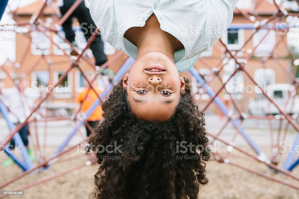 outdoor portrait: cute schoolgirl at climber, looking at camera stock photo