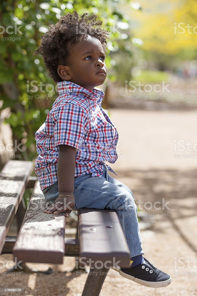 Outdoor portrait of a black little boy sited stock photo