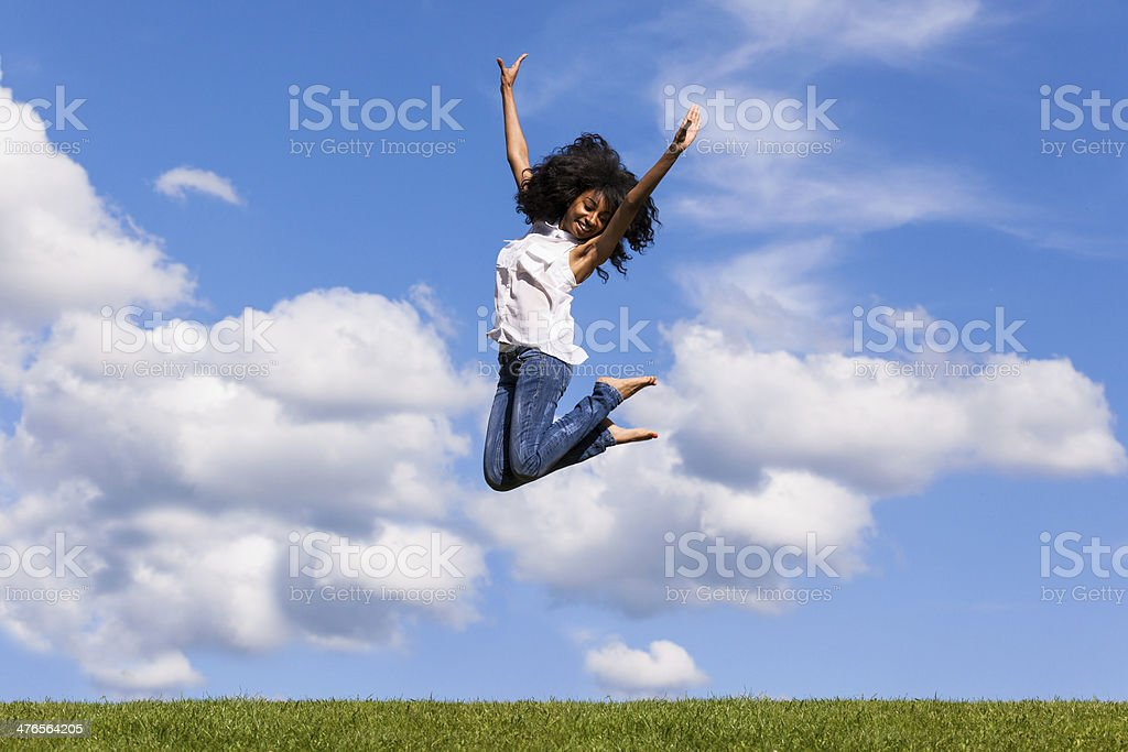 Outdoor portrait of a teenage black girl jumping stock photo