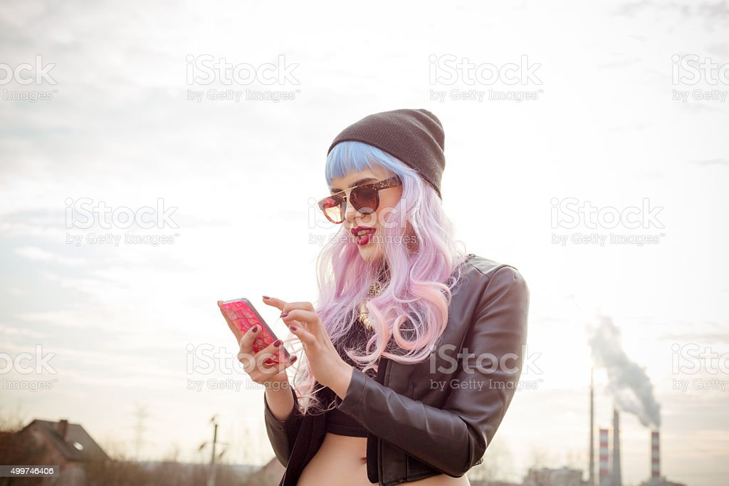 Outdoor portrait of blue-pink hair cool girl texting on phone stock photo