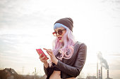 Outdoor portrait of blue-pink hair cool girl texting on phone