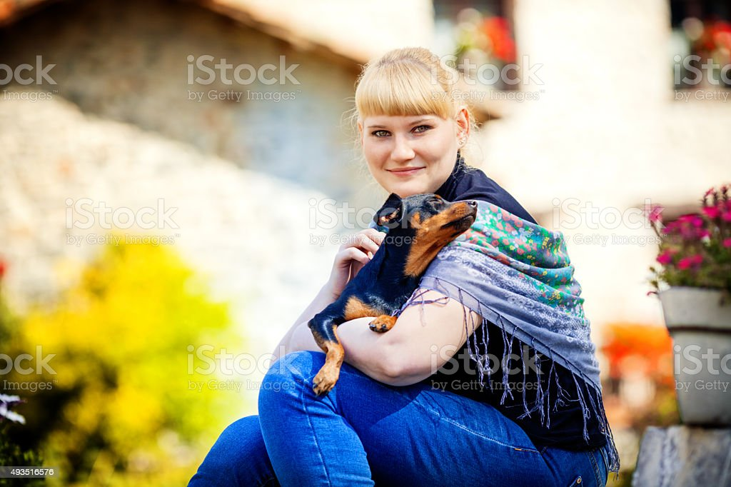 Outdoor portrait of cute female with dog stock photo