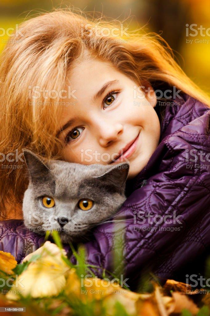 Outdoor Portrait of Little Girl Hugging Her Cat stock photo