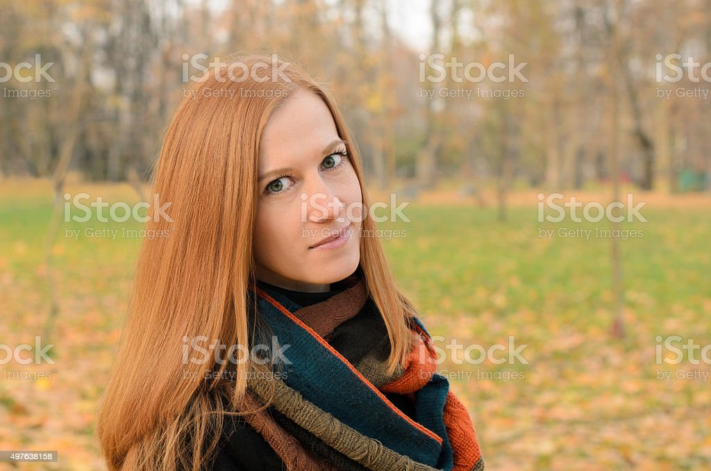 Outdoor portrait of red haired woman with green eyes stock photo