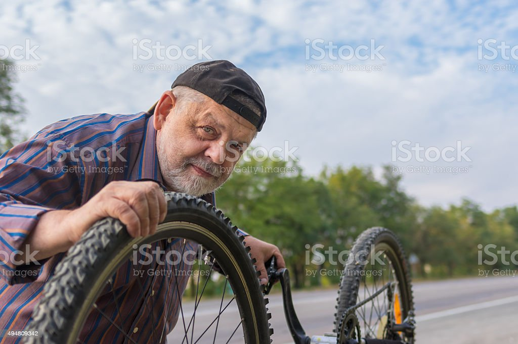 Outdoor portrait of senior bicycle mechanic at work stock photo