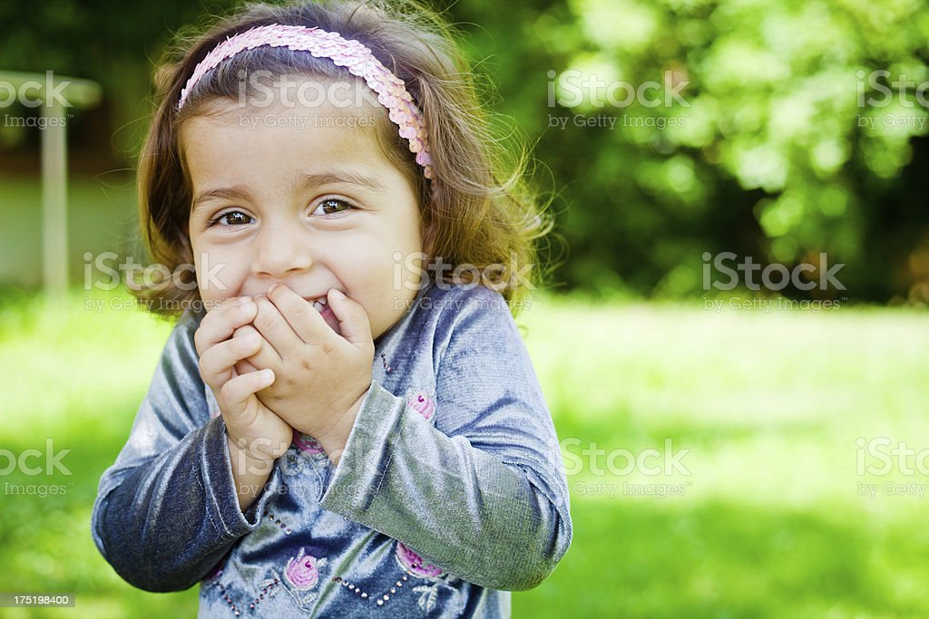 Outdoor Portrait of Small Cheerful Indian Girl hands on mouth stock photo