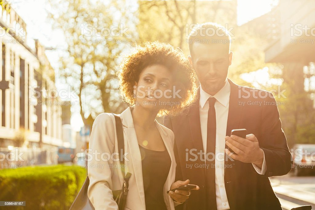 Outdoor portrait of two business people with smart phones stock photo