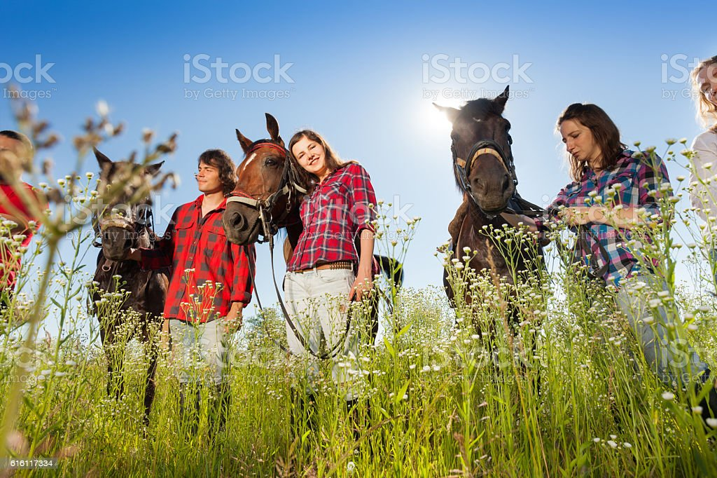 Outdoor portrait of young people with their horses stock photo