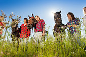 Outdoor portrait of young people with their horses