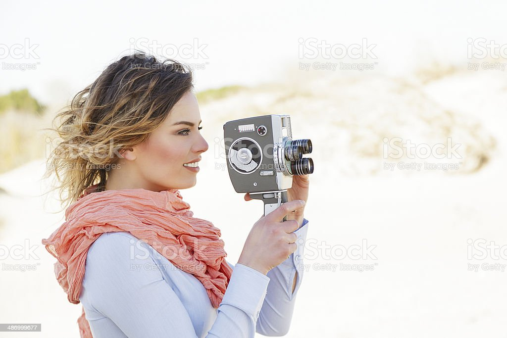 Outdoor Portrait of young woman holding vintage 8mm camera stock photo