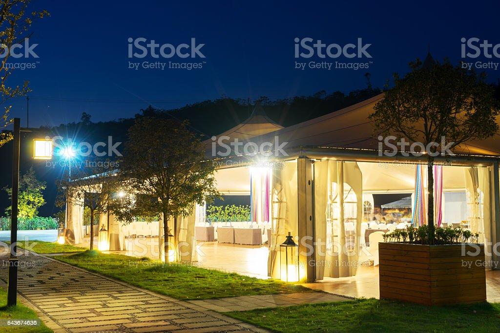 outdoor restaurant under huge tent at night stock photo