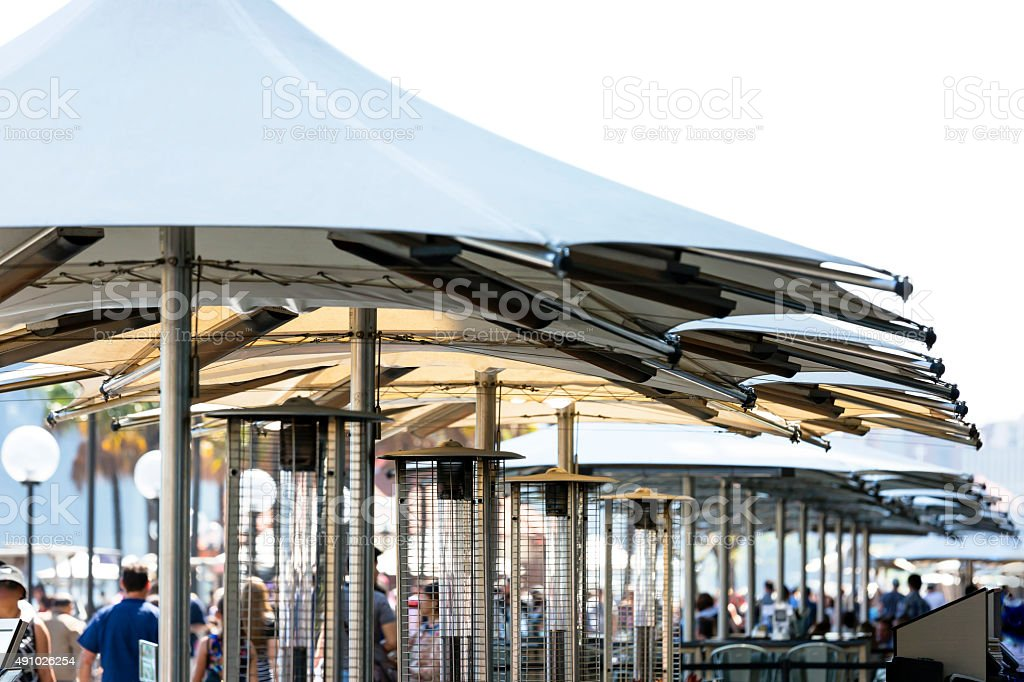 Outdoor restaurant with gas heaters and outdoor umbrellas, copy space stock photo
