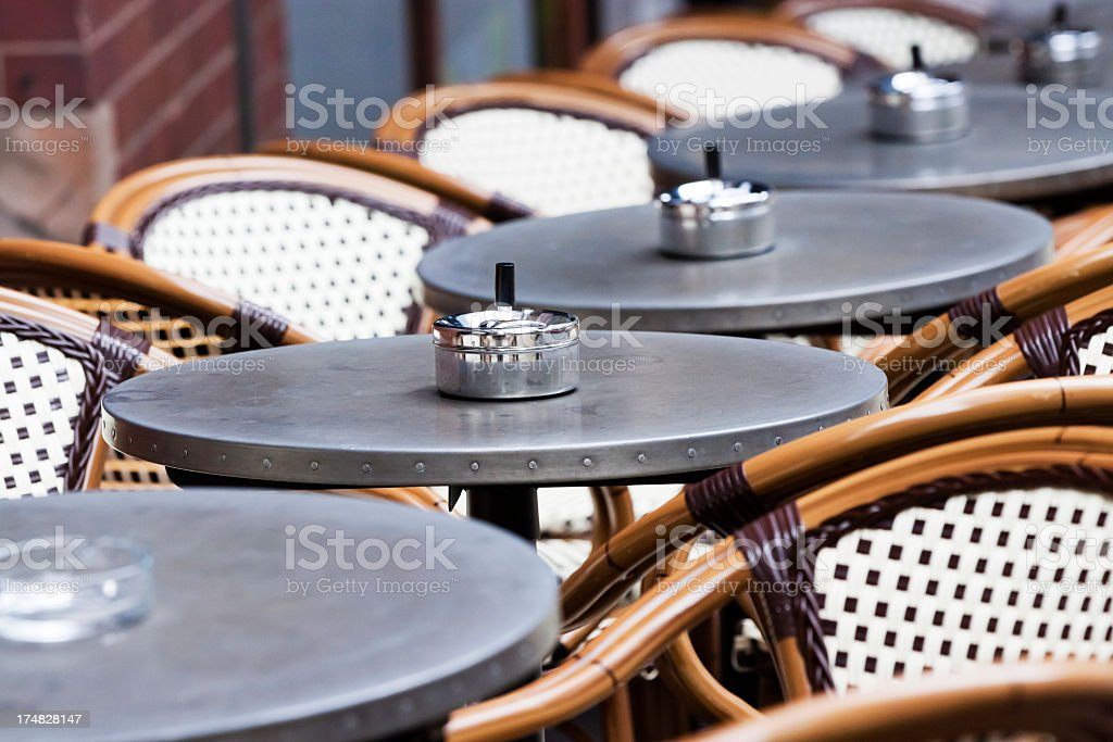 Outdoor restaurant with row of tables, ashtrays and cane chairs royalty-free stock photo