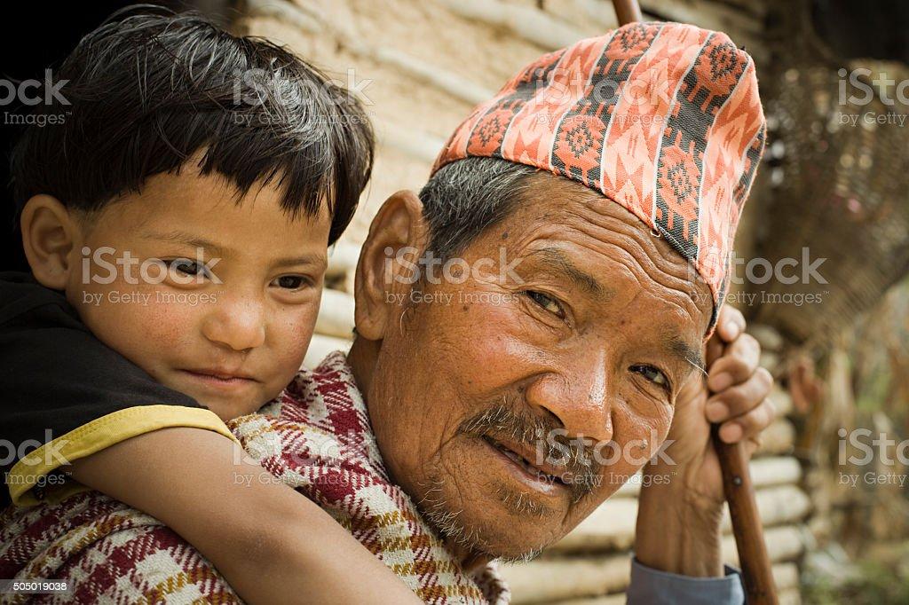 Outdoor rural image of grandchild on grandfather's piggyback. stock photo