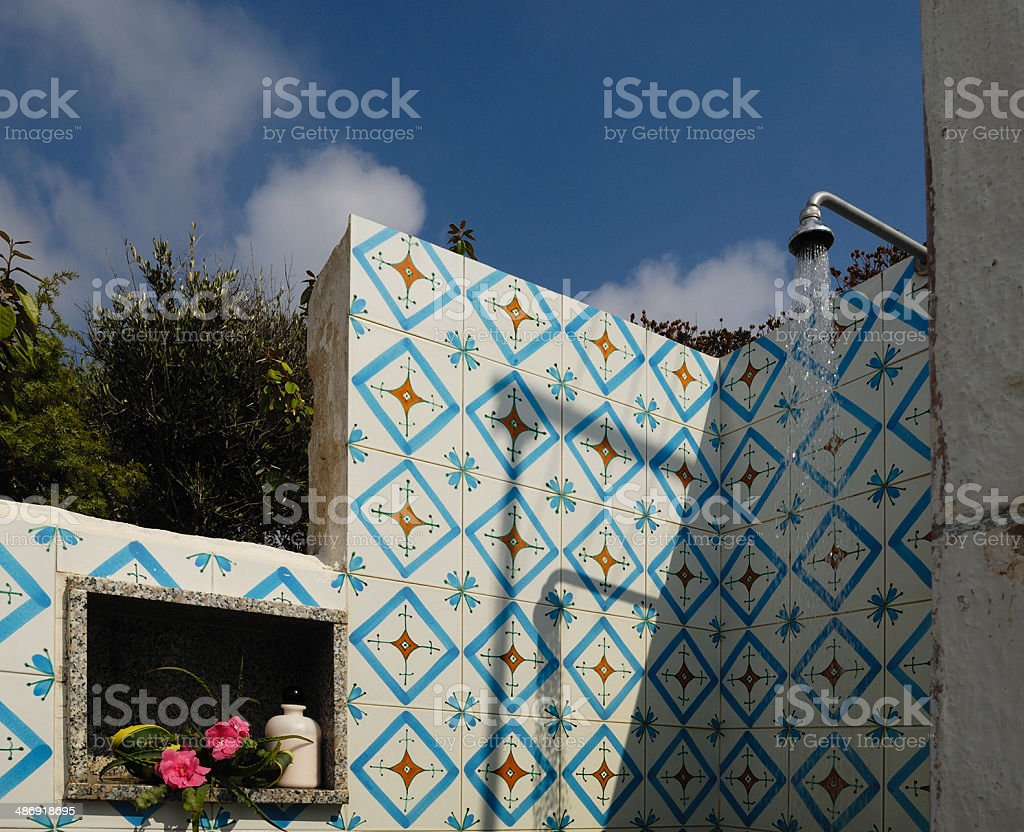 Outdoor shower with colorful tiles, seaside house, blue sky background royalty-free stock photo