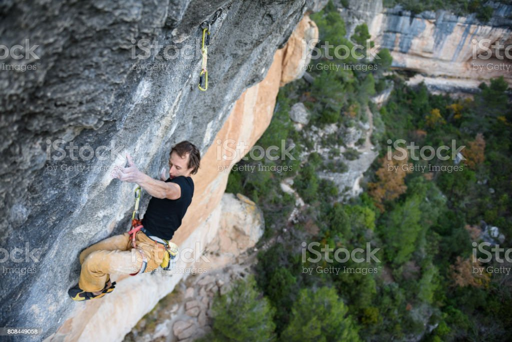 Outdoor sport activity. Rock climber ascending a challenging cliff. Extreme sport climbing. stock photo
