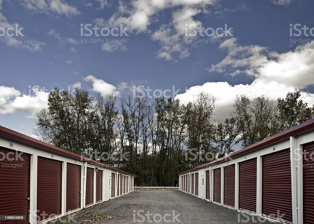 Outdoor storage units with red doors and blue sky and trees stock photo