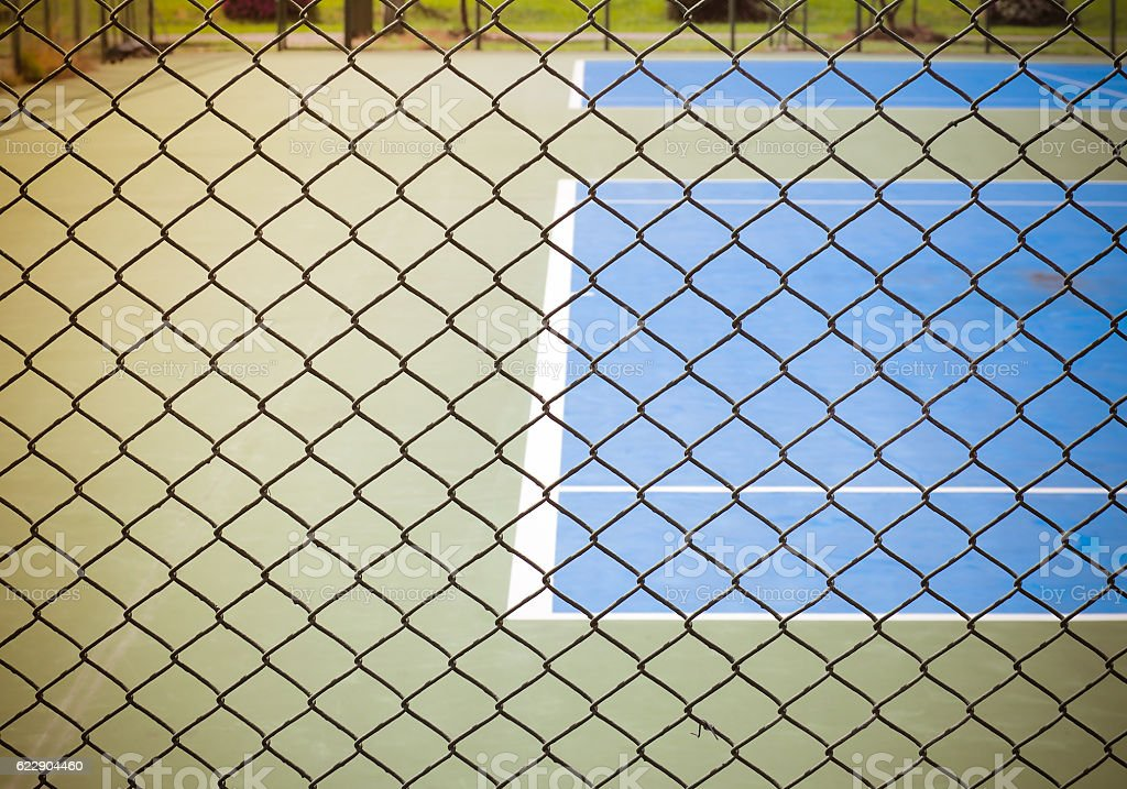 Outdoor tennis sport court behind wired fence stock photo