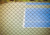 Outdoor tennis sport court behind wired fence