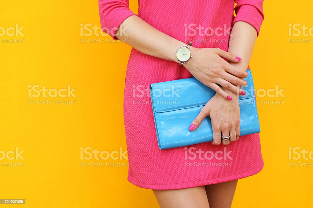 Outdoor trendy girl near yellow street wall .Stylish pink dress stock photo