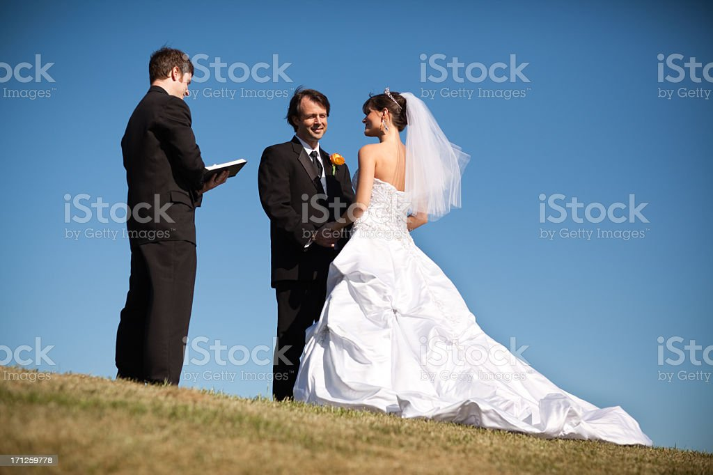 Outdoor Wedding of Happy Bride and Groom, With Minister stock photo