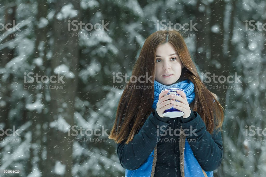 Outdoor winter portrait of freezing young lady holding cup stock photo