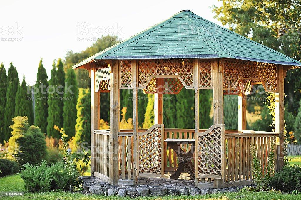 Outdoor wooden gazebo over summer landscape background stock photo