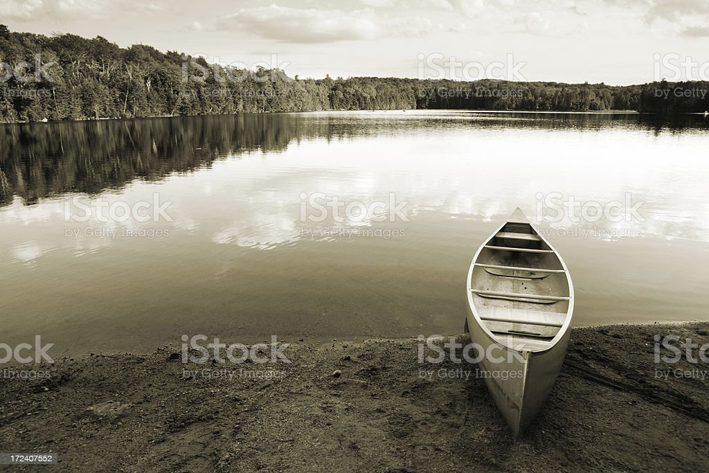 Outdoors canoe beside lake sepia tone royalty-free stock photo